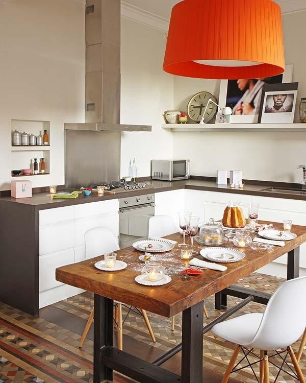 Cocina con mesa de estilo industrial, sillas plastic Eames y lámpara pantalla cinta.