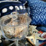 decoración, cristal y caracolas, cojines azul denim