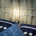 Cabecero de forja gris patinado y cojines azul índigo