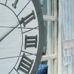 Reloj de pared de estilo industrial junto a telas visillos rayas.